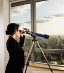 Picture of a woman looking through a telescope. The woman is wearing a dark coat, has her hair up in a bun, and is holding on to the eye piece of a telescope in her high rise office. She is looking through the telescope at the city below.